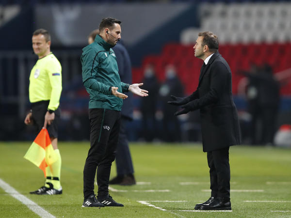Basaksehir team manager Okan Buruk (right) argues with referee Sebastian Coltescu during a Champions League soccer match between Paris Saint Germain and Istanbul Basaksehir in Paris on Tuesday.