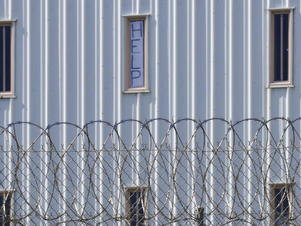 "A sign reading ""HELP"" is posted in the window of an inmate's cell during a 2019 tour with state officials at Holman Correctional Facility in Atmore, Ala."