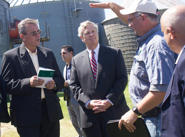 Then U.S. Secretary of Agriculture Tom Vilsack (center) and Cuban Agriculture Minister Gustavo Rodriguez Rollero (left) listen to Central Iowa farmer Aaron Lehman during a tour of Lehman's farm on June 3, 2016.