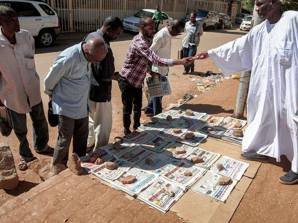 People in Sudan's capital, Khartoum, browse newspapers with headlines featuring the 2020 U.S. general election results. After 27 years, the State Department has removed Sudan from a list of state sponsors of terrorism.