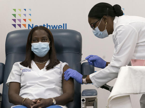 Sandra Lindsay (left) a nurse at Long Island Jewish Medical Center, is inoculated with the Pfizer-BioNTech COVID-19 vaccine by Dr. Michelle Chester on Monday in New York.