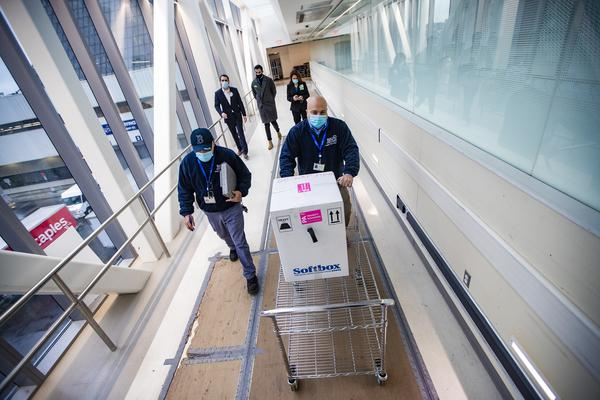 Richard Guarino, Boston Medical Center supply chain operations associate director, wheels a cart containing Pfizer's COVID-19 vaccine to the pharmacy. (Jesse Costa/WBUR)