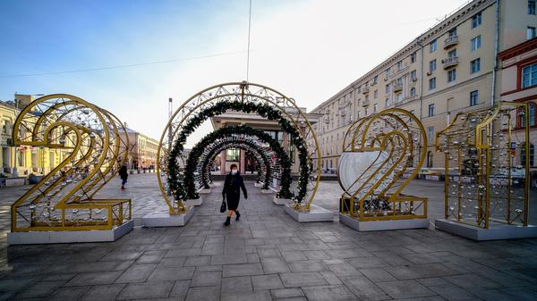 A woman wearing a face mask walks past a New Year's decoration in central Moscow on Friday.