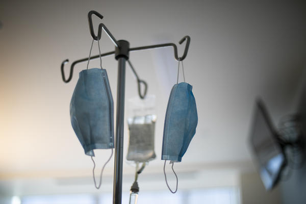 Face masks hang from an IV pole at a hospital.