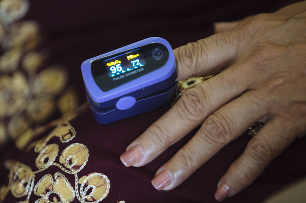 A paramedic uses a pulse oximeter to check a patient's vital signs during an August home visit in the Bronx borough of New York.
