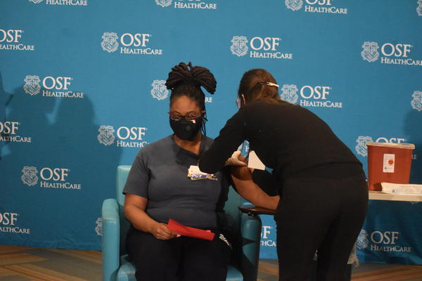 Chemica Jones, a 42-year-old CNA at OSF Saint Francis Medical Center, shuts her eyes tight as Shannon Lesch, an RN BSN, administers the COVID-19 vaccine on Tuesday, Dec. 15, 2020.