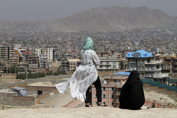 Afghan women look at the skyline of Kabul in September.