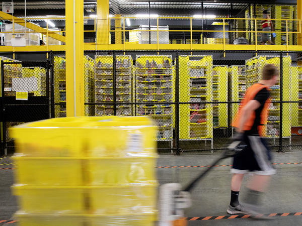A worker pulls a pallet jack with plastic crates at an Amazon warehouse in Robbinsville, N.J. The company is facing its biggest labor battle yet with a unionization vote expected at a facility in Alabama.