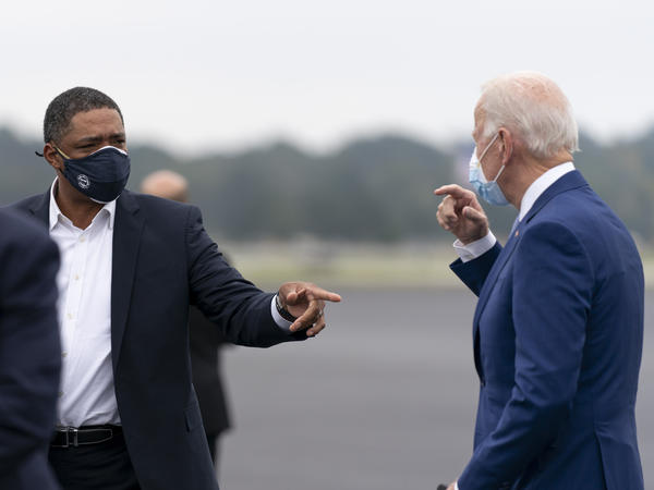 Rep. Cedric Richmond, left, speaks with Joe Biden at Columbus Airport in Columbus, Ga., in October. Biden's transition team says he has not had close contact with Richmond, who has tested positive for the coronavirus.