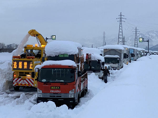 A snowplow clears a path beside cars stranded Friday on the snow-covered Kan-etsu Expressway in the city of Minamiuonuma in Japan's Niigata prefecture.