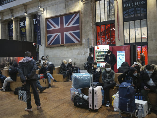 Passengers wearing face masks wait next to the Eurostar Terminal at Gare du Nord train station in Paris on Monday. France is banning all travel from the U.K. for 48 hours in an attempt to make sure a new strain of the coronavirus in Britain doesn't reach its shores.