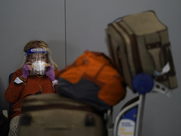 A traveler adjusts her mask while waiting to check in for her flight at the Los Angeles International Airport on Nov. 23.
