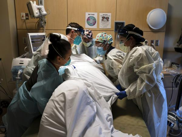 Hospital workers move a patient into the prone (face down) position, which can help increase the lung capacity of some COVID-19 patients. The medical team was photographed Nov. 19 at Providence Holy Cross Medical Center in Los Angeles.