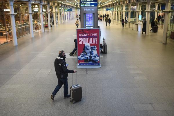A man walks past a sign at St. Pancras train station in London, England.