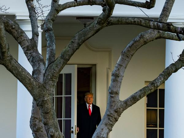 President Trump emerges from the Oval Office on Wednesday as he departs the White House en route to Florida's Mar-a-Lago, where he will spend Christmas and New Year's Eve.