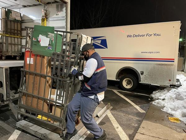 Like many of his colleagues, postal worker Rickey Ramirez is working overtime to keep up with the crush of Christmas deliveries. Many packages are likely to be delivered after Dec. 25.