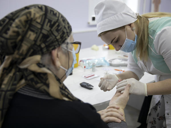 A woman undergoes antibody testing before an injection of the Russian COVID-19 vaccine known as Sputnik V at an outpatient clinic in Grozny earlier this week.