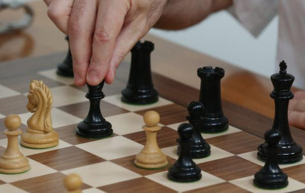 Grandmaster chess player Garry Kasparov makes a move in a match against grandmaster Fabiano Caruana during the final day of the Grand Chess Tour at the Chess Club and Scholastic Center in St. Louis.