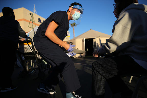 A California National Guard medic prepares to check the vital signs of an incoming patient in front of triage tents outside St. Mary Medical Center last week in Apple Valley amid a surge in COVID-19 patients in Southern California.