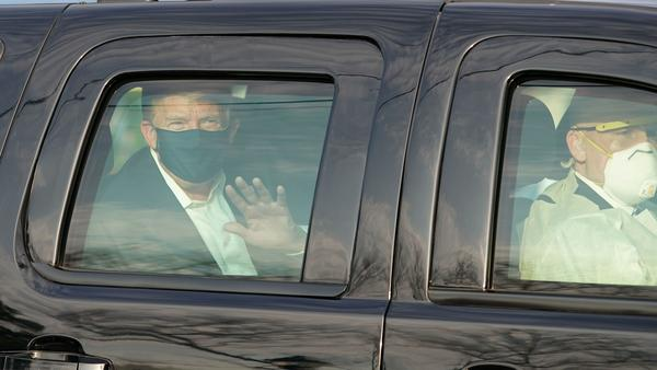 Dr. James Phillips is no longer working at Walter Reed National Military Medical Center, months after criticizing President Trump's flouting of coronavirus safety guidelines. Here, Trump waves to supporters from an SUV in October as he was driven outside the facility in Bethesda, Md.