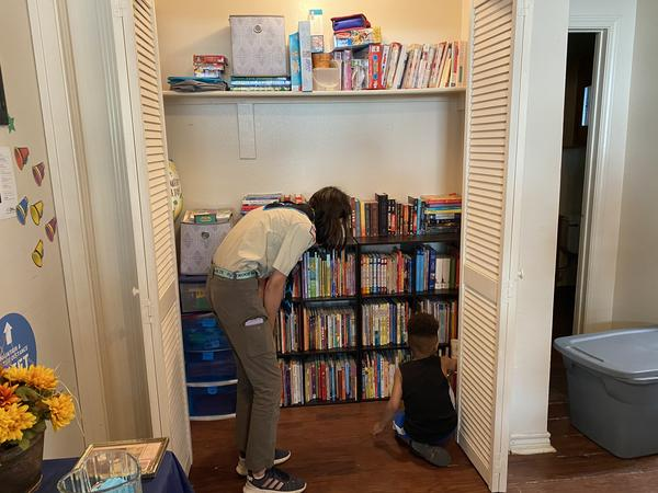 Madison Knefley helps a young boy pick out a book from the shelves she filled earlier that day.