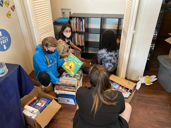 Others scouts from Troop 890 help Madison Knefley sort through books and organize them on the shelves. She put together the community library for her eagle project — one of the last requirements she needed to finish to receive her Eagle Scout rank and pin at a ceremony in February.