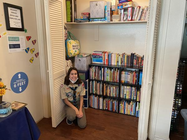Madison Knefley sits in front of her finished eagle project: a library in the community room at a Lake Highlands public housing complex.