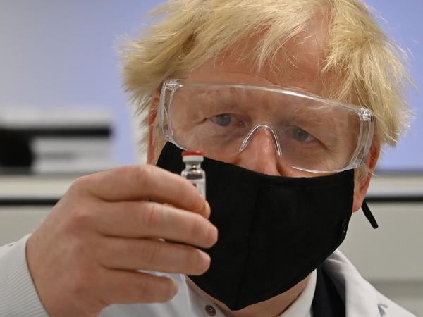 U.K. Prime Minister Boris Johnson looks at the newly authorized AstraZeneca/Oxford University COVID-19 vaccine.