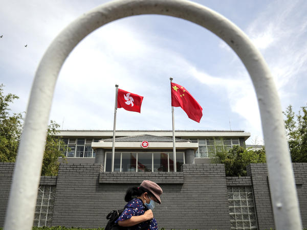 A woman wearing a face mask walks by the Government of Hong Kong Special Administrative Region office building in Beijing in June following the imposition of a national security law on Hong Kong. Ten Hong Kong fugitives were sentenced to prison Wednesday for illegally crossing international boundaries.