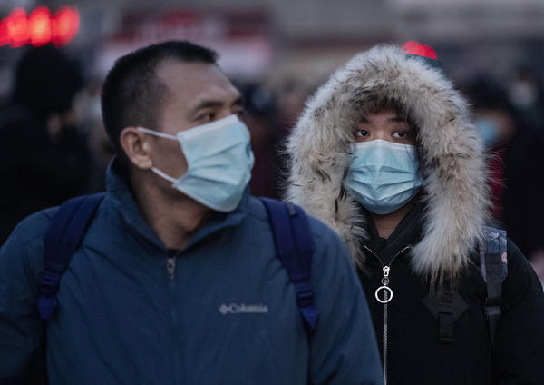 Chinese travelers at a railway station in Beijing, China, wear face masks to protect themselves from the new coronavirus on Jan. 21, 2020. The virus was first identified in Wuhan, China, in Dec. 2019, and since then has quickly spread worldwide.