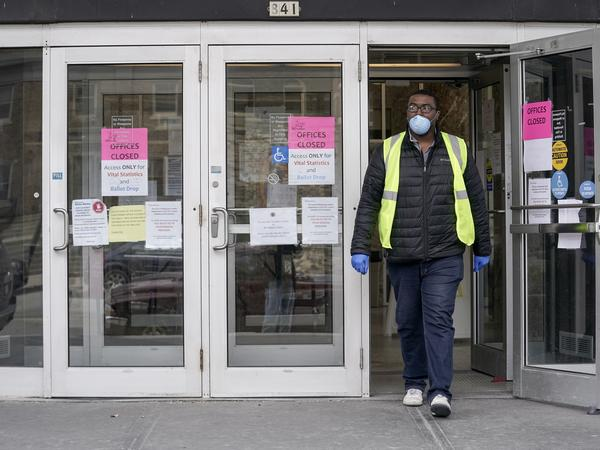 A worker leaves the the Frank P. Zeidler Municipal Building in Milwaukee late last month. Gov. Tony Evers has suspended in-person voting in the state's primary, which was scheduled for Tuesday April 7.