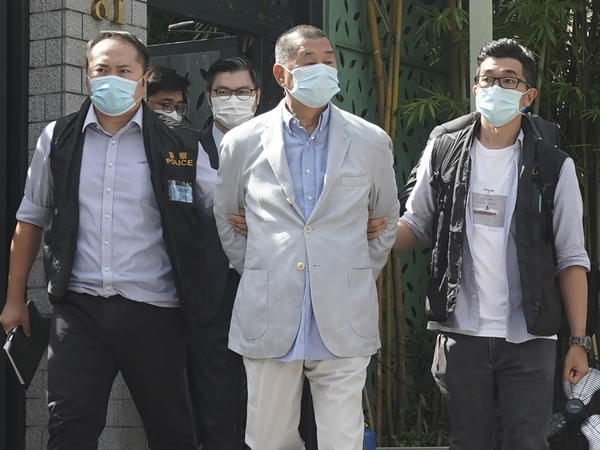 Hong Kong media tycoon Jimmy Lai (center) is arrested at his home in Hong Kong on Monday. Hong Kong police raided the publisher's headquarters in the highest-profile use yet of the new national security law Beijing imposed on the city after protests last year.