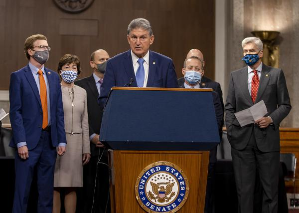 West Virginia Sen. Joe Manchin, who's seen here alongside a group of Democratic and Republican members of Congress as they announce a proposal for a COVID-19 relief bill on Dec. 1, said Sunday that negotiations on the bill's text are ongoing.