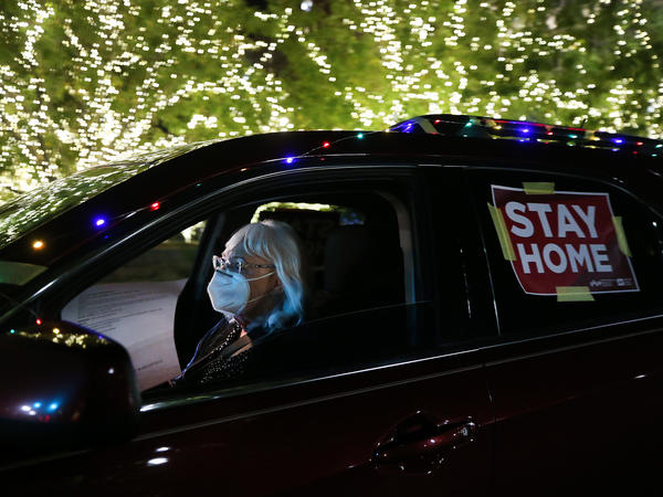 "A ""Stay Home"" sign is taped to a driver's vehicle as she passes Christmas lights during a car caravan of nurses calling for people to remain home amid a coronavirus surge last month in El Paso, Texas."