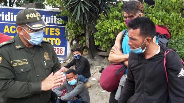 Jose Paéz (right), who migrated from Venezuela, pleads with a Colombian police officer. He was detained with about 50 other people at a roadblock in Pamplona.