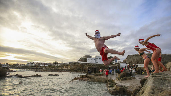 People take part in the annual Christmas Day swim at the Forty Foot bathing spot in Sandycove Dublin, Ireland, Dec. 25, 2020.