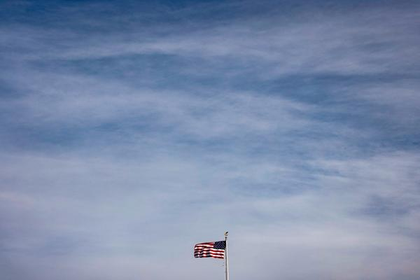 The American flag flies above the White House in Washington, DC.