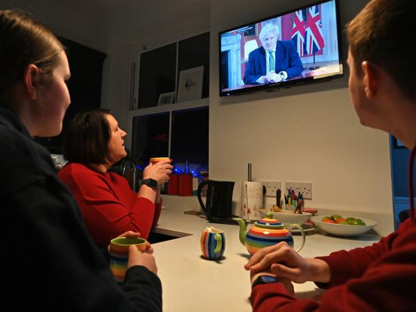 A family gathers around the television Monday in Liverpool, England, to watch Prime Minister Boris Johnson speak to the nation about the new lockdown.