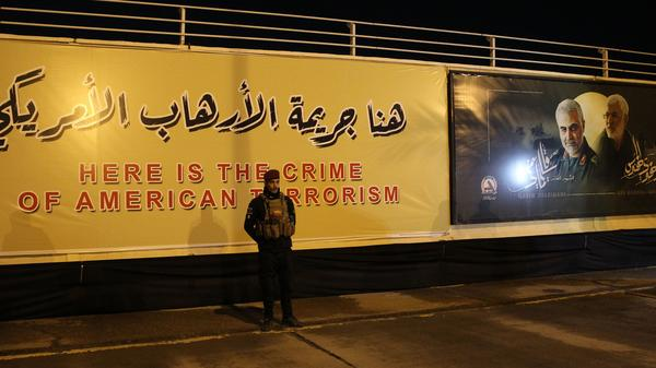 Iran is seeking to detain President Trump over the U.S. killing of top Iranian military commander Qassem Soleimani. Here, an Iraqi fighter stands in front of a banner at the site of the drone strike at Baghdad International Airport.
