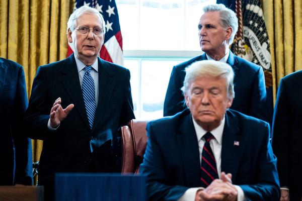 Senate Majority Leader Mitch McConnell (R-KY) speaks as House Minority Leader Kevin McCarthy (R-CA) U.S. President Donald Trump listen during a signing ceremony for H.R. 748, the CARES Act in the Oval Office of the White House  in Washington, DC.