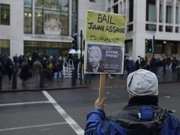 A Julian Assange supporter holds up a placard of the WikiLeaks founder outside Westminster Magistrates Court, the site of his bail hearing, in London on Wednesday.
