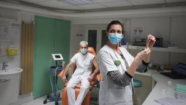 """A nurse prepares to administer the Pfizer-BioNTech COVID-19 vaccine to Dr. Jean-Christophe Richard in La Croix-Rousse hospital, in Lyon, France, on Wednesday. Amid public outcry, France's health minister promised Tuesday an """"exponential"""" acceleration of his country's slow coronavirus vaccination process."""