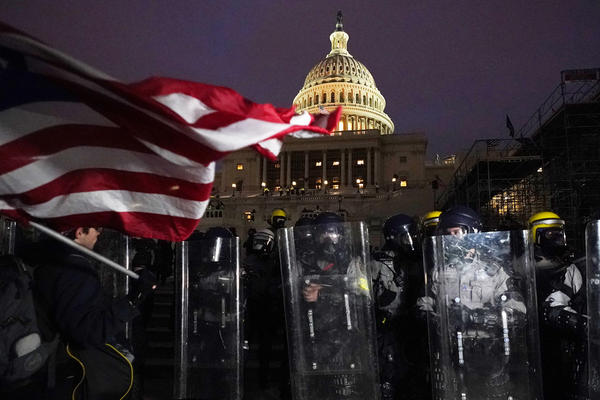 Police stand behind their shields outside the Capitol after a day of rioting on Wednesday.