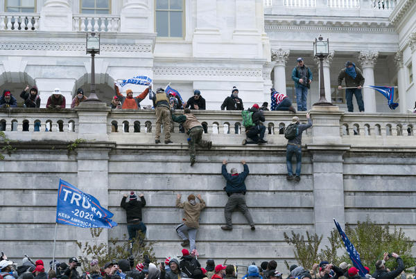 Rioters climb the west wall of the the U.S. Capitol. The rioters far outnumbered and swiftly overwhelmed the Capitol Police as they charged up the steps, smashed windows, broke into the Senate chamber and occupied offices.