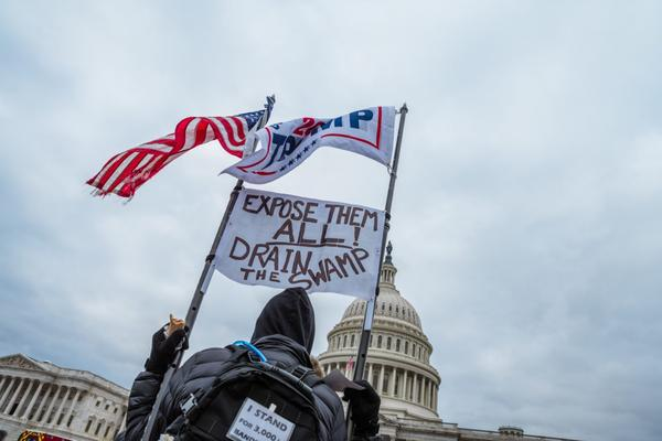A man holding signs and flags in support of President Donald Trump is seen in front of the Capitol Building in Washington, DC.
