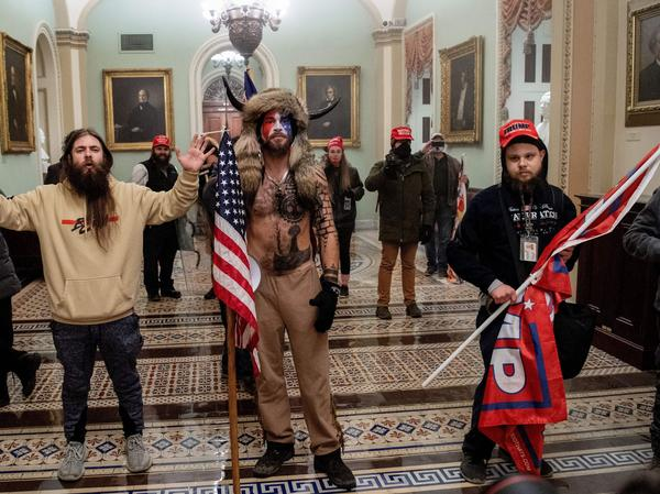 Supporters of President Trump, including Jake Angeli (center), a QAnon supporter known for his painted face and horned hat, stand inside the U.S. Capitol on Jan. 6. Demonstrators breached security and entered the Capitol as Congress was in the process of tallying the 2020 electoral vote count.