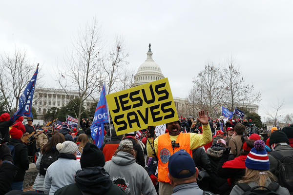 """A yellow banner that reads """"JESUS SAVES"""" stands out in the pro-Trump mob outside the U.S. Capitol on Wednesday."""