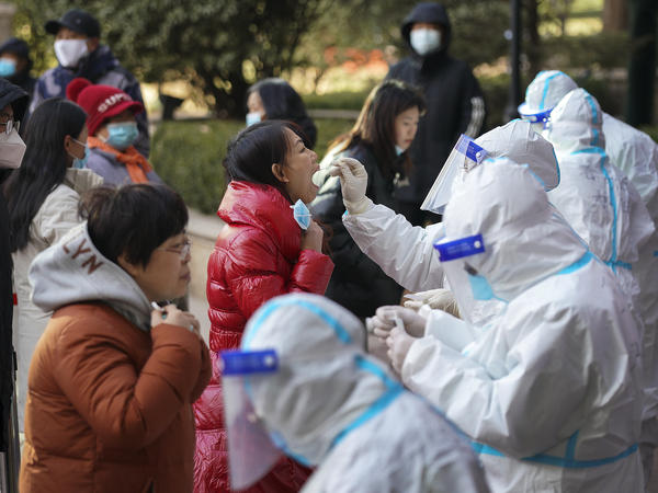In this photo released by Xinhua News Agency, medical workers take swabs from residents in Shijiazhuang in north China's Hebei province on Jan. 6. Authorities have announced new restrictions to contain the coronavirus.