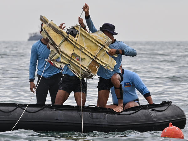 Indonesian Navy divers hold wreckage from Sriwijaya Air flight 182 during a search and rescue operation at sea near Lancang island on Sunday.