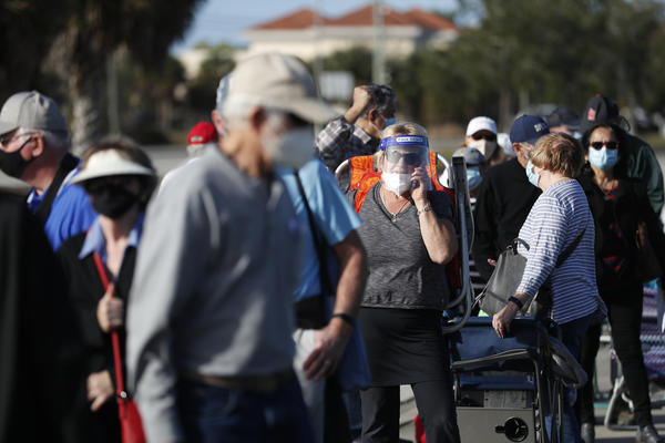 Older adults and first responders wait in line to receive a COVID-19 vaccine late last month at the Lakes Regional Library in Fort Myers, Fla.